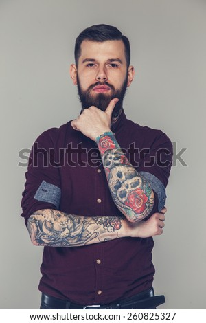 Male with tattoed hands and beard posing - stock photo