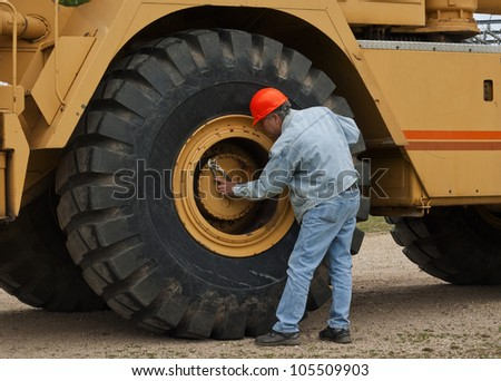 male worker doing maintenance on a large piece of machinery - stock photo