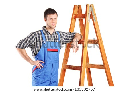 Male worker in jumpsuit standing next to a ladder isolated on white background - stock photo
