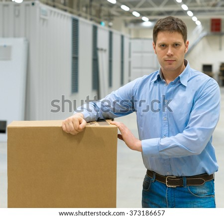 Male worker with boxes at warehouse. - stock photo