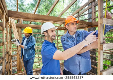 Male workers working in incomplete timber cabin at construction site - stock photo