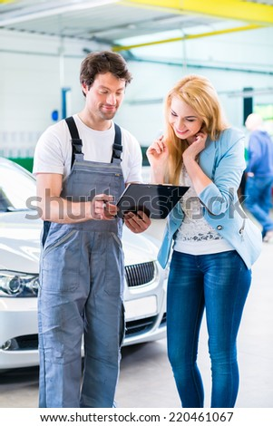 Male workshop mechanic handover car with checklist to client  - stock photo