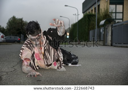 Male zombie crawling on his knees, on empty city street, looking at camera reaching out one hand. Halloween theme - stock photo