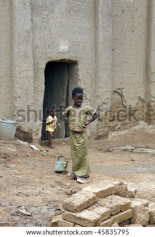MALI - AUGUST 17: Children at the door of a house August 17, 2009 in Djenne, Mali. The city of Djenne heritage of mankind is built with adobe and wood. - stock photo