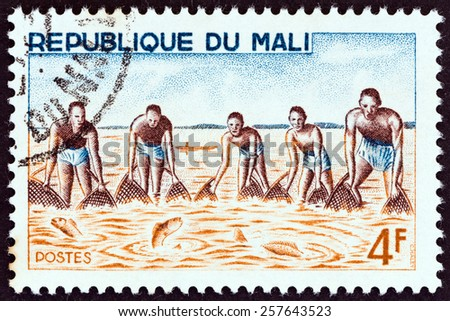 """MALI - CIRCA 1966: A stamp printed in Mali from the """"River Fishing """" issue shows collective shore fishing, circa 1966.  - stock photo"""