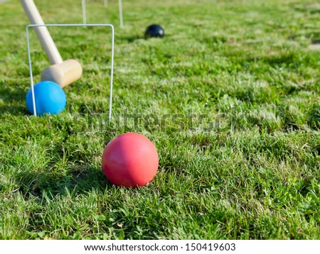 mallet and balls in game of croquet on green lawn in summer day - stock photo