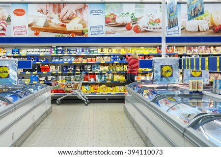 MALMEDY, BELGIUM - JULY 29, 2015: Interior of a Lidl supermarket. Shopper in the refrigerated fresh products aisle. Lidl is a German discount chain, 9800 stores, in 28 countries in Europe. - stock photo