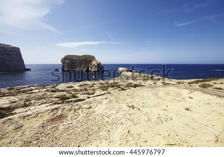 Malta Island, Gozo, Dweira, tourists on the rocky coastline near the Azure Window Rock - stock photo