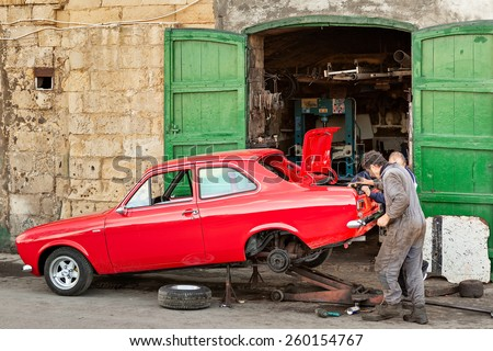 MALTA - JANUARY 21 2015: Two mechanics restoring old vintage red car near their garage at Valetta, Malta - stock photo
