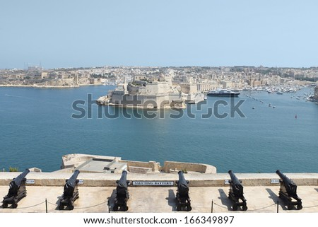 Malta, La Valletta amazing fortified city. Scenic view of the Grand Harbour, Fort St. Angelo and Birgu (Citta Vittoriosa) waterfront, from the British saluting battery in the Upper Barrakka gardens. - stock photo