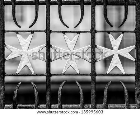 Maltese Cross pattern on wrought iron gate in Valletta - stock photo