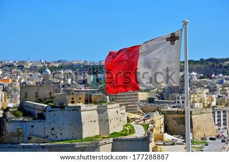 Maltese flag and Senglea (Isla) cityscape - stock photo