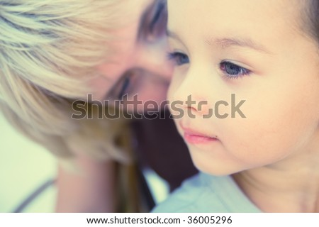 Mam to whisper in son's ear. Focus on child. Special processing - stock photo