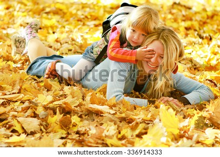 Mama and her little daughter lying on the leaves in autumn - stock photo