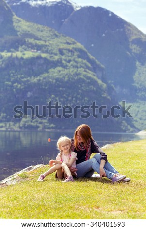 Mama with daughter sitting on the shore fjord, Norway - stock photo