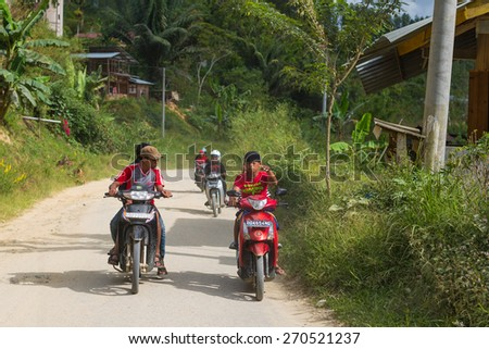 Mamasa, Sulawesi, Indonesia - August 18, 2014: Group of boys riding scooters on a country road in Mamasa, West Tana Toraja, South Sulawesi, Indonesia. - stock photo