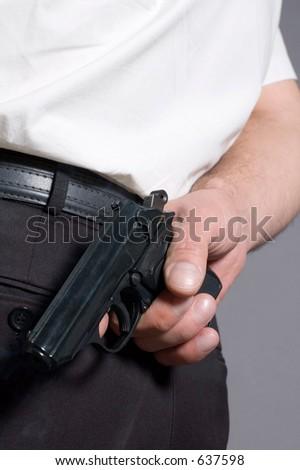 Man a hiding pistol behind a back - stock photo