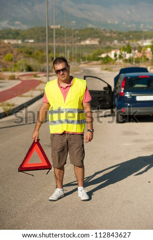 Man about to set up a breakdown triangle - stock photo