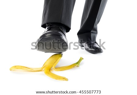 Man about to step on banana peel isolated on white background.   - stock photo