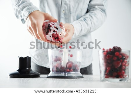Man adds frozen berriess to focused blender pot with before making make tasty smoothie drink to refresh in summer time. Unfocused glass with frozen berries in front near - stock photo