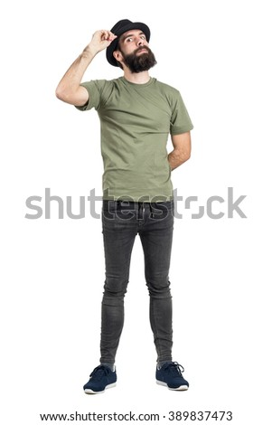 Man adjusting hat with head leaned back staring intense at camera. Full body length portrait isolated over white studio background. - stock photo