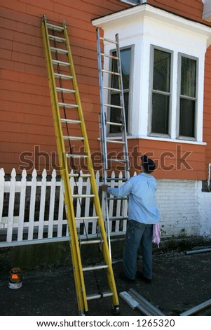 man adjusting ladder painting outside of house - stock photo