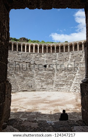 Man admiring the ancient theater of Aspendos through a doorway - stock photo