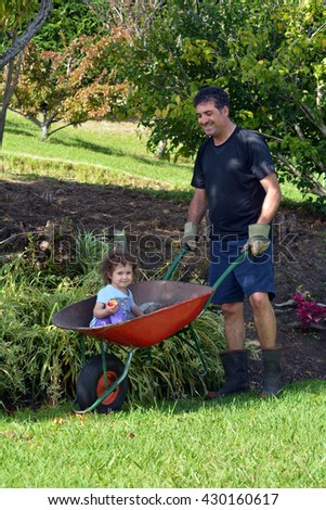 Man (age 40-45) carry his daughter (1-2) in a wheelbarrow during gardening work in the garden - stock photo