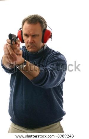Man aiming a pistol at shooting range - stock photo