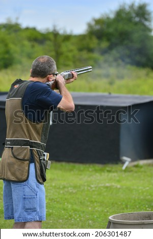 Man aiming at a target and shooting an automatic rifle for - stock photo