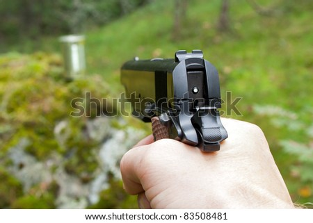 Man aims at a metal can with loaded handgun in the woods - stock photo