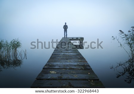 Man alone standing on the end of a jetty during a foggy, gray morning. - stock photo