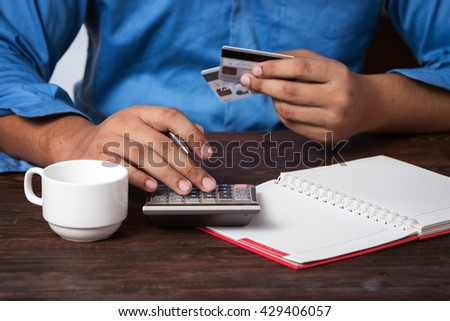 Man analyzing his payment by credit card. accounting. - stock photo
