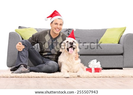 Man and a dog with Santa hats sitting by a sofa isolated on white background - stock photo