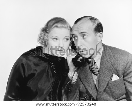 Man and a woman eavesdropping on the telephone - stock photo