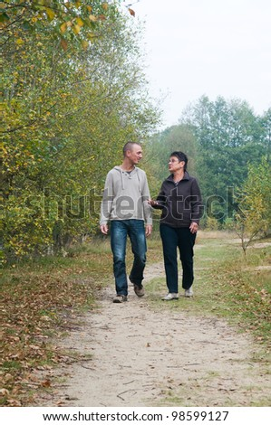 Man and a woman having a walk in the forest. - stock photo