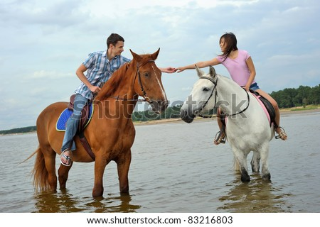 Man and a woman in the sea on horseback - stock photo