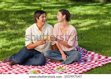 Man and a woman laughing while raising their glasses of orange juice during a picnic - stock photo