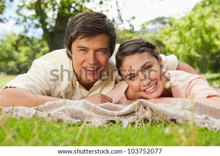 Man and a woman lying prone together on a blanket in the grass while smiling - stock photo