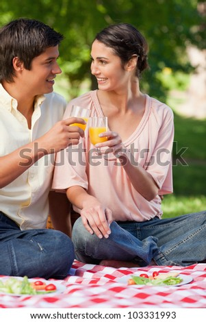 Man and a woman smiling while they touch glasses of orange juice during a picnic - stock photo