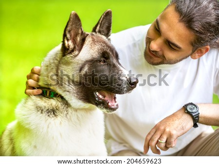 Man and Akita Inu dog  walk in the park. He keeps the dog on the leash. - stock photo