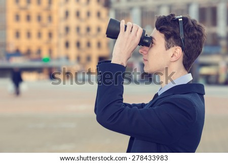 Man and binoculars. Business man with binoculars in his hand against the background of the streets downtown. Man holding binoculars. Concept - looking for a job. Man with spying. Service monitoring. - stock photo