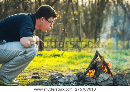 Man and bonfire in spring forest. Coals of fire. Sunset in Ukraine - stock photo