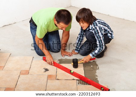 Man and boy laying ceramic floor tiles together - stock photo