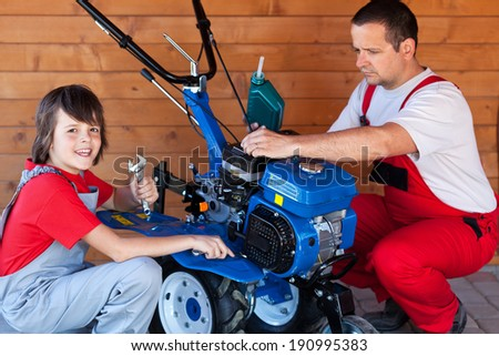 Man and boy preparing a cultivator machine for work - adding oil and fastening loose screws - stock photo