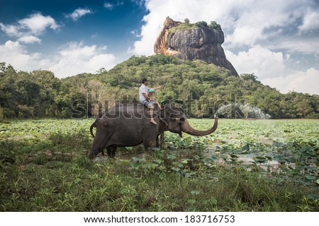 Man and child riding on the back of elephant with rock of Sigiriya as backdrop - stock photo