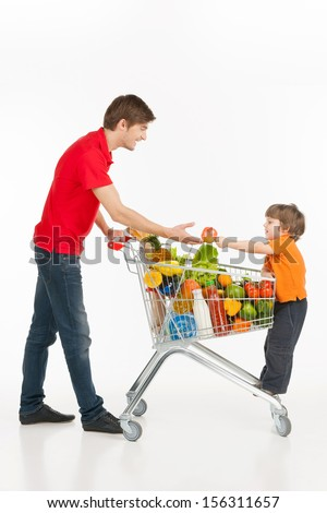 Man and child shopping. Cheerful young man and little boy carrying shopping cart full of goods and smiling while isolated on white - stock photo