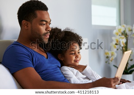 Man and daughter sitting in bed watching computer, waist up - stock photo
