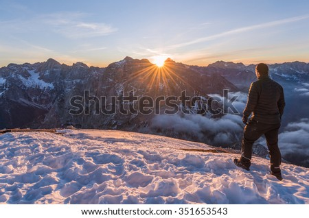 Man and dog enjoying the sunrise on top of the mountain. - stock photo