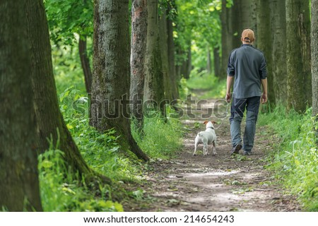 man and dog walking on park - stock photo